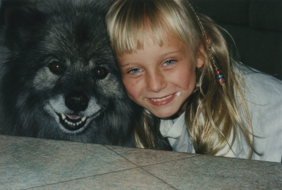 Two happy faces, keeshond dog & girl.